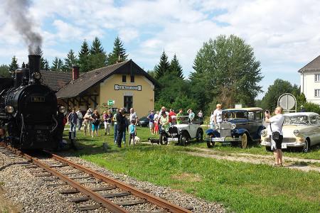 Dampfzug mit Oldtimern auf Straße und Schiene am 4. August 2019