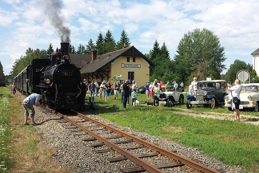 Dampfzug mit Oldtimern auf Straße und Schiene